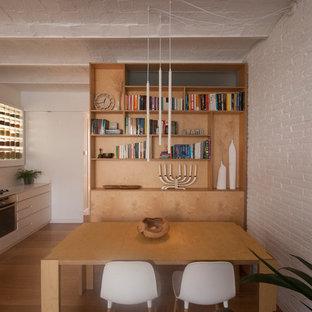 Modelo de comedor de cocina abovedado y ladrillo, escandinavo, de tamaño medio, ladrillo, con paredes blancas, suelo de madera en tonos medios y ladrillo