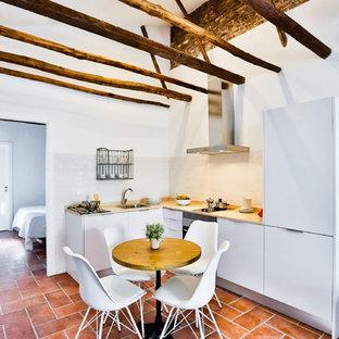 Foto di una piccola sala da pranzo aperta verso la cucina mediterranea con pareti bianche, pavimento in terracotta e nessun camino