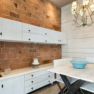 Ejemplo de comedor urbano, sin chimenea, con paredes beige y suelo de madera en tonos medios