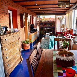 Immagine di una sala da pranzo aperta verso il soggiorno bohémian con pareti arancioni, pavimento con piastrelle in ceramica, nessun camino e pavimento blu