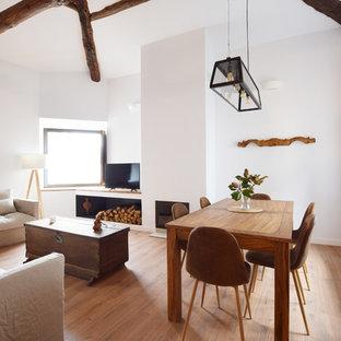 Diseño de comedor mediterráneo, de tamaño medio, con paredes blancas, suelo de madera en tonos medios, estufa de leña y marco de chimenea de yeso