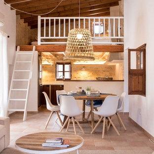 Modelo de comedor mediterráneo, abierto, sin chimenea, con paredes blancas y suelo de baldosas de terracota
