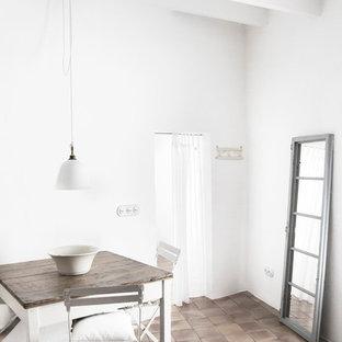 Imagen de comedor mediterráneo, pequeño, abierto, sin chimenea, con paredes blancas y suelo de baldosas de terracota