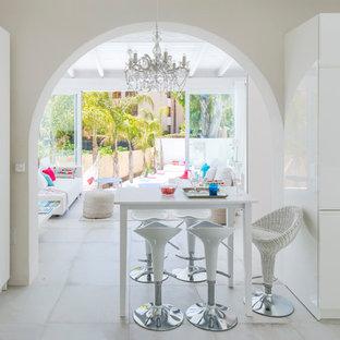 Imagen de comedor mediterráneo, de tamaño medio, abierto, con suelo de baldosas de cerámica, suelo blanco y paredes blancas