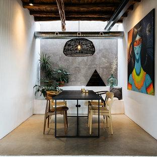 Ejemplo de comedor mediterráneo con paredes blancas, suelo de cemento y suelo gris