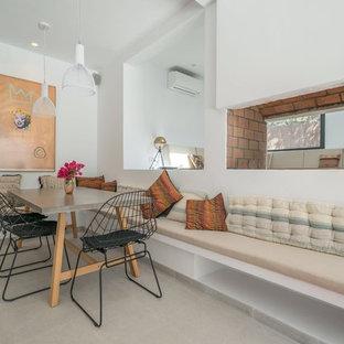 Foto de comedor contemporáneo con paredes blancas, suelo de cemento, chimenea de doble cara, marco de chimenea de ladrillo y suelo gris