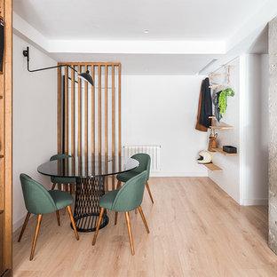 Tropenstil Esszimmer mit weißer Wandfarbe und braunem Holzboden in Madrid