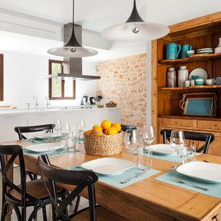 Ejemplo de comedor mediterráneo, grande, abierto, con paredes blancas y suelo gris