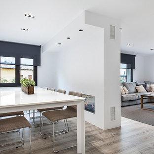 Aménagement d'une salle à manger ouverte sur le salon scandinave de taille moyenne avec un mur blanc, un sol en bois brun et une cheminée double-face.