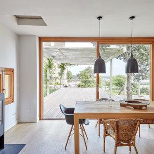 Ejemplo de comedor mediterráneo, de tamaño medio, con paredes blancas, suelo de madera clara, estufa de leña, marco de chimenea de metal y suelo beige