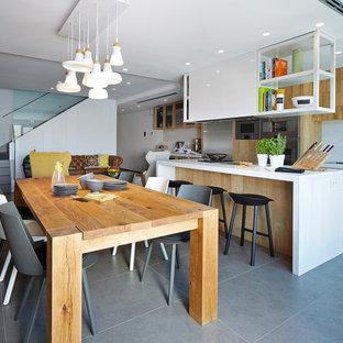 Immagine di una grande sala da pranzo aperta verso il soggiorno contemporanea con pareti bianche, pavimento con piastrelle in ceramica e nessun camino