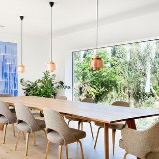 Imagen de comedor actual, sin chimenea, con paredes blancas, suelo beige y suelo de madera clara