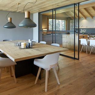 Modelo de comedor de estilo de casa de campo, grande, abierto, con suelo de madera clara, paredes grises y suelo marrón