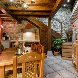 Inspiration pour une salle à manger ouverte sur la cuisine chalet de taille moyenne avec un mur orange, un sol en carreau de terre cuite et aucune cheminée.