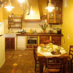 セビリアの中サイズのラスティックスタイルのおしゃれなダイニングキッチン (黄色い壁、濃色無垢フローリング、暖炉なし) の写真
