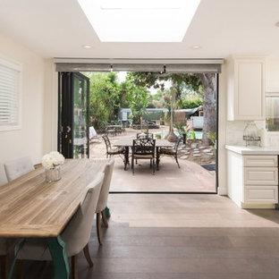 Esempio di una grande sala da pranzo aperta verso la cucina tropicale con pareti bianche, pavimento in laminato, nessun camino e pavimento marrone