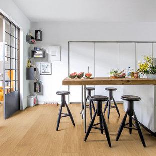 Diseño de comedor de cocina actual, grande, sin chimenea, con paredes blancas y suelo de madera en tonos medios