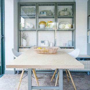 Immagine di una sala da pranzo aperta verso il soggiorno industriale di medie dimensioni con pareti bianche e nessun camino