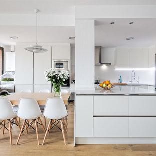 Ejemplo de comedor de cocina nórdico con paredes blancas, suelo de madera clara y suelo beige