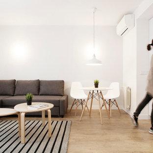 Imagen de comedor escandinavo, pequeño, abierto, sin chimenea, con paredes blancas y suelo de madera en tonos medios