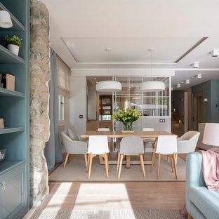 Immagine di una grande sala da pranzo aperta verso il soggiorno nordica con pareti blu, pavimento in laminato, nessun camino e pavimento marrone