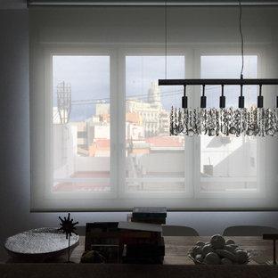 Ispirazione per una sala da pranzo aperta verso la cucina di medie dimensioni con pareti bianche, pavimento in laminato e pavimento marrone