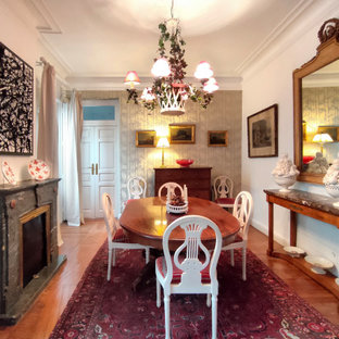 Ispirazione per una sala da pranzo chic chiusa e di medie dimensioni con pareti multicolore, pavimento in legno massello medio, camino classico e cornice del camino in pietra ricostruita
