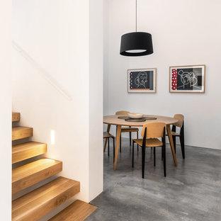 Diseño de comedor actual, sin chimenea, con paredes blancas, suelo de cemento y suelo gris
