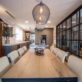 Modelo de comedor de cocina actual, grande, con paredes blancas, suelo de madera clara y suelo beige