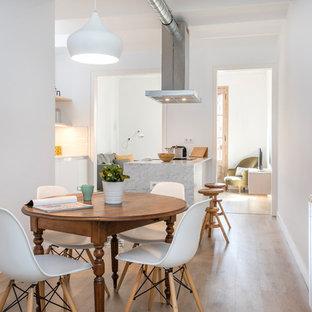 Ejemplo de comedor de cocina contemporáneo, de tamaño medio, sin chimenea, con paredes blancas, suelo marrón y suelo de madera clara