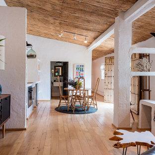 Diseño de comedor mediterráneo, abierto, con paredes blancas y suelo de madera clara