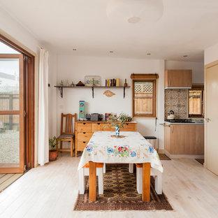 Imagen de comedor mediterráneo, de tamaño medio, abierto, sin chimenea, con paredes blancas, suelo laminado y suelo beige