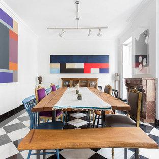 Ejemplo de comedor ecléctico, grande, con paredes blancas, suelo de baldosas de porcelana, chimenea tradicional, marco de chimenea de piedra y suelo multicolor