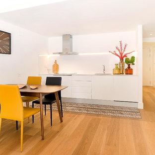Ejemplo de comedor de cocina actual, de tamaño medio, con paredes blancas, suelo de madera en tonos medios y suelo marrón