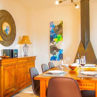 Foto di una sala da pranzo aperta verso il soggiorno costiera di medie dimensioni con pareti beige, pavimento in marmo, camino classico e cornice del camino in metallo