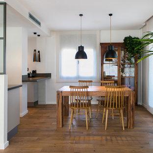 Modelo de comedor contemporáneo, de tamaño medio, abierto, sin chimenea, con paredes blancas y suelo de madera en tonos medios