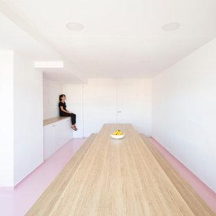 Ejemplo de comedor de cocina escandinavo, de tamaño medio, con paredes blancas y suelo rosa