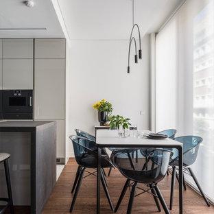 Modelo de comedor de cocina actual, sin chimenea, con paredes blancas, suelo de madera en tonos medios y suelo marrón
