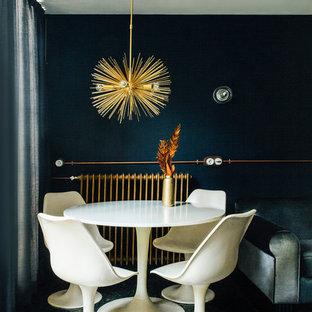 Imagen de comedor contemporáneo con paredes azules y suelo negro