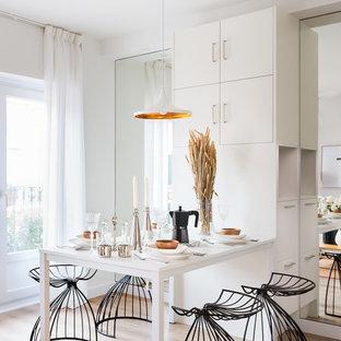 Modelo de comedor actual, pequeño, con paredes blancas, suelo beige y suelo de madera clara