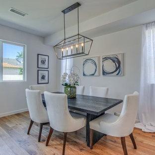 Ispirazione per una sala da pranzo aperta verso la cucina design di medie dimensioni con pareti bianche, pavimento in legno massello medio, camino sospeso, cornice del camino in metallo e pavimento marrone