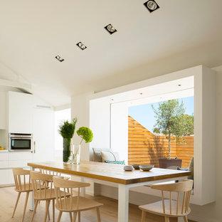Ejemplo de comedor de cocina contemporáneo, de tamaño medio, sin chimenea, con paredes blancas y suelo de madera clara