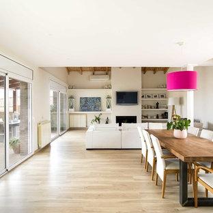 Modelo de comedor actual, abierto, con suelo de madera clara, chimenea tradicional, marco de chimenea de yeso, paredes beige y suelo beige
