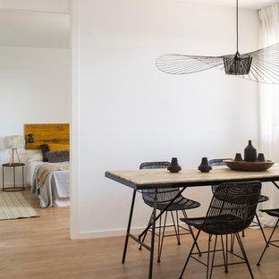 Modelo de comedor actual, de tamaño medio, con paredes blancas y suelo de madera en tonos medios