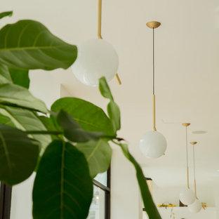 Imagen de comedor contemporáneo, de tamaño medio, abierto, con paredes blancas, suelo de baldosas de porcelana, chimenea tradicional, marco de chimenea de hormigón y suelo gris