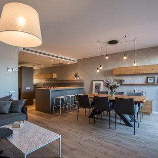 Modelo de comedor contemporáneo, grande, abierto, con paredes grises, suelo laminado, chimenea de doble cara, marco de chimenea de metal y suelo marrón