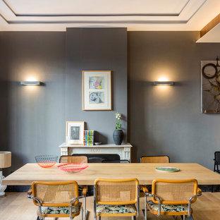 Imagen de comedor contemporáneo, abierto, con paredes grises, suelo de madera clara, chimenea tradicional y suelo beige
