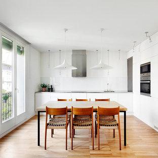 Diseño de comedor de cocina actual, de tamaño medio, sin chimenea, con suelo de madera en tonos medios y paredes blancas