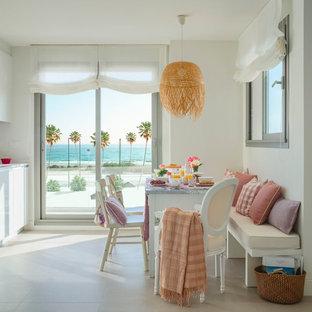 Imagen de comedor de cocina costero con paredes blancas y suelo beige