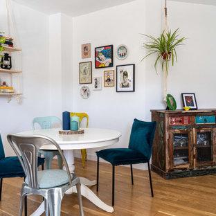Imagen de comedor bohemio con paredes blancas, suelo de madera en tonos medios y suelo marrón